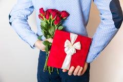 Valentinsgrußtagesgeschenküberraschung, versteckendes Geschenk des Mannes und Halten des roten rosafarbenen Blumenstraußes stockbild