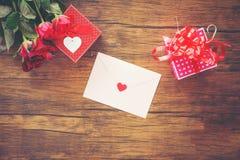 Valentinsgrußtagesgeschenkboxrot und -ROSA auf roter rosafarbener Blume und Geschenkbox der hölzernen Valentinsgrußtageskarte stockfotografie