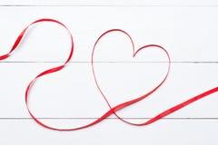 Valentinsgrußtagesherz formte Band über weißem Holztisch stockfotografie