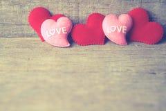 Valentinsgrußtageshintergrund mit den roten und rosa Herzen auf hölzernem BAC Lizenzfreie Stockfotos