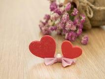 Valentinsgrußtageshintergrund mit roten Herzen auf Holzfußboden und unscharfen rosa Rosen im Hintergrund Zu küssen Mann und Frau  Lizenzfreies Stockfoto
