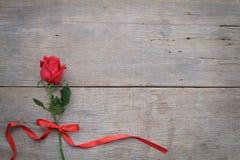 Valentinsgrußtageshintergrund mit Rotrose und Band auf hölzernem Lizenzfreies Stockfoto