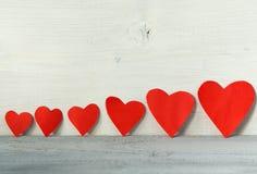 Valentinsgrußtageshintergrund, rote Herzen in einer Linie auf einem hellen hölzernen Hintergrund Lizenzfreies Stockbild
