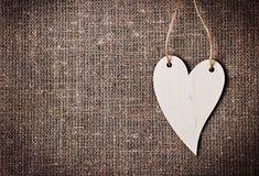 Valentinsgrußtageskarte mit Herzen auf einem Rausschmiß oder einem Hintergrund des groben Sackzeugs oder der Leinwand Stockfotos