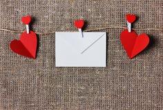 Valentinsgrußtageskarte mit Herzen auf einem Rausschmiß oder einem Hintergrund des groben Sackzeugs oder der Leinwand Stockfotografie