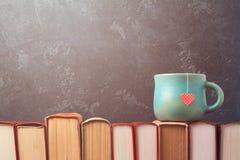 Valentinsgrußtageskonzept mit Teeschale auf Büchern über Tafel Lizenzfreies Stockbild