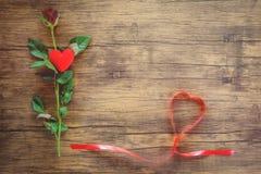 Valentinsgrußtagesrote rosafarbene Blume auf hölzernem rotem Herzen mit Rosen und rotem Bandherzen auf Draufsichtkopienraum stockbild