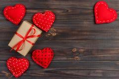 Valentinsgrußtagesweinlesehintergrund mit Herzen und eine Geschenkbox auf Holztisch Stockfotografie