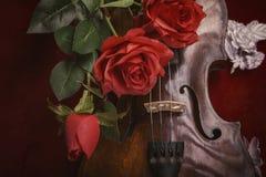 Valentinsgrußvioline mit roten Rosen auf einem dunkelroten Hintergrund Lizenzfreies Stockbild
