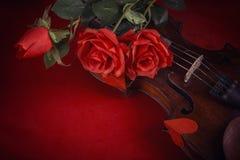 Valentinsgrußvioline mit roten Rosen auf einem dunkelroten Hintergrund Stockfotos