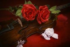 Valentinsgrußvioline mit roten Rosen auf einem dunkelroten Hintergrund Lizenzfreie Stockbilder