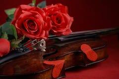 Valentinsgrußvioline mit roten Rosen auf einem dunkelroten Hintergrund Lizenzfreie Stockfotos