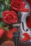 Valentinsgrußvioline mit roten Rosen auf einem dunkelroten Hintergrund Stockfotografie