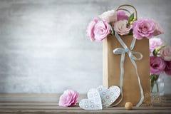 Valentinsgruß-Tageshintergrund mit Rosen Blumen und Herzen Stockfotografie