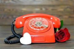 Valentinsgruß-Tageskarte: Weinlesetelefon, Rotrose und ein Herz Lizenzfreies Stockfoto