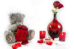 Valentinsgruß-Tagesteddybär-, -rosen-Blumenstrauß im Vase, Herzen und Kerzen auf weißem Hintergrund Lizenzfreie Stockfotos