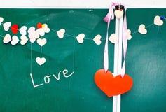 Valentinstag. Herz des Papierhängens am Tafelhintergrund Lizenzfreies Stockbild