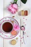 Valentinstag: Romantischer Tee, der mit Makrone und Herzen trinkt Stockbild