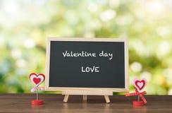 Valentinstag und LIEBE simsen auf schwarzen Brett- und Holztischplatte wi Stockbild