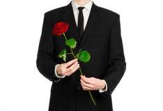 Valentinstag- und Tagesthema der Frauen: die Hand des Mannes in einer Klage, die eine rote Rose lokalisiert auf weißem Hintergrun Lizenzfreies Stockfoto