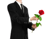 Valentinstag- und Tagesthema der Frauen: die Hand des Mannes in einer Klage, die eine rote Rose lokalisiert auf weißem Hintergrun Lizenzfreie Stockfotos