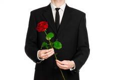 Valentinstag- und Tagesthema der Frauen: die Hand des Mannes in einer Klage, die eine rote Rose lokalisiert auf weißem Hintergrun Stockfotografie