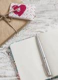 Valentinstaggeschenke im Kraftpapier, in der selbst gemachten Valentinstagkarte und in einem sauberen offenen Notizbuch Lizenzfreie Stockbilder