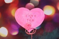 Valentinstaggrußkarte in Form eines rosa Herzens mit einer Aufschrift lieben Sie in einem Stand, der vom rosa Flamingo gemacht wi lizenzfreie stockfotos