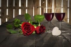 Valentinstagherzrosen und Rotwein Stockfotografie