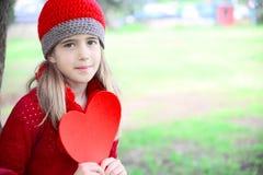 Valentinstagmädchen, das großes Herz hält Stockfotos