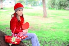 Valentinstagmädchen, das großes Herz hält Stockfoto