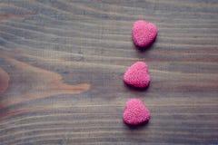 Valentinstagsüßigkeitsherzen auf einem hölzernen Hintergrund Stockfotos