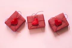 Valentinstagzusammensetzung: drei rote Geschenkboxen, Bögen des roten Seils und rote Herzen auf Pastellrosahintergrund Beschneidu Lizenzfreie Stockfotografie
