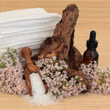 Valerian Spa Treatment. Valerian flower spa arrangement with aromatherapy essential oil bottle, sea salt, driftwood and towel stack over bamboo background Stock Photo