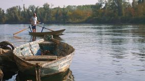 Valesana die op een typische Italiaanse boot op de rivier Ticino in Italië roeit stock footage