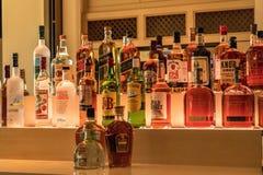 Valet av färgrika starkspritalkoholflaskor fodrar hyllan av a royaltyfri bild