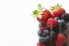 Valet av sommar bär frukt i exponeringsglas mot vit bakgrund Arkivfoton