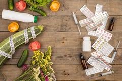 valet mellan den sunda livsstilen och läkarbehandlingar, grönsaker eller preventivpillerar på det bruna träskrivbordet arkivfoto