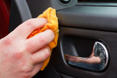 Valeting the car. Cleaning the car interior with polishing cloth Royalty Free Stock Photo