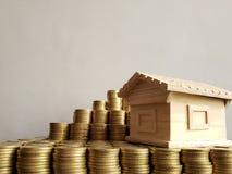valeur d'une propriété, pièces de monnaie empilées et une figure en bois d'une maison images stock