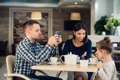 Valeurs familiales modernes Engendrez dépendant au sujet d'utiliser le PC de comprimé d'appareils électroniques, tandis que son é photos stock