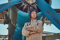 Valiant handsome pilot in a full flight gear standing with crossed arms near military airplane. Royalty Free Stock Photos