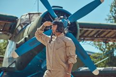 Valiant handsome pilot in a full flight gear standing near a retro military airplane and looks away. Royalty Free Stock Image