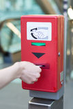 Validate a ticket at a red ticket validation machine for the und Royalty Free Stock Photo