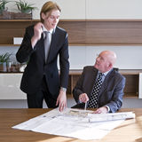 Validating designs. Young architect asking his boss to validate his designs, and discussing it animatedly, gesturing with his hand Stock Image