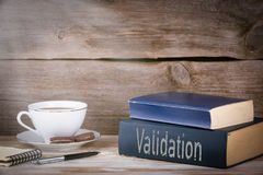 Validation. Stack of books on wooden desk stock photography