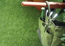 Valigia attrezzi di giardinaggio con il fondo di estate dell'erba verde Immagine Stock Libera da Diritti