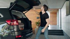 Valigia caucasica di caricamento dell'uomo in automobile nera in garage di lusso archivi video