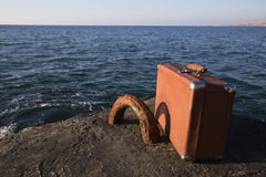 Valigia che sta sulla spiaggia Immagine Stock