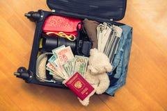 Valigia con l'orsacchiotto di cose e un passaporto straniero Fatture asiatiche del cento-dollaro e dei soldi per il viaggio Conce fotografia stock libera da diritti